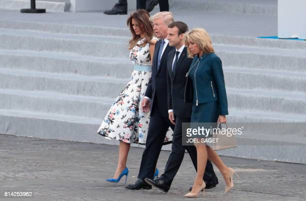 TOPSHOT US First Lady Melania Trump US President Donald Trump French President Emmanuel Macron and his wife Brigitte Macron leave the tribune after...
