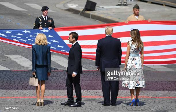 US First Lady Melania Trump US President Donald Trump French President Emmanuel Macron and his wife Brigitte Macron stand in front of the US national...
