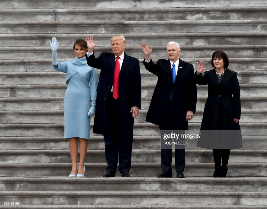 First Lady Melania Trump, US President Donald Trump, Vice President Mike Pence and his wife Karen, wave goodbye to former President Barack Obama's helicopter as it departs from the US Capitol after Trump's inauguration ceremonies at the US Capitol in Washington, DC, on January 20, 2017. / AFP PHOTO / Robyn BECK