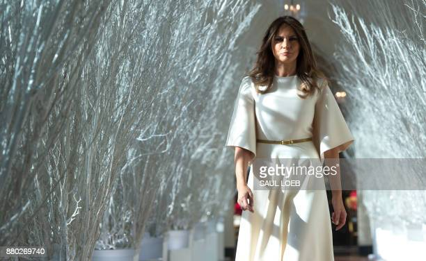 US First Lady Melania Trump walks through Christmas decorations in the East Wing as she tours holiday decorations at the White House in Washington DC...