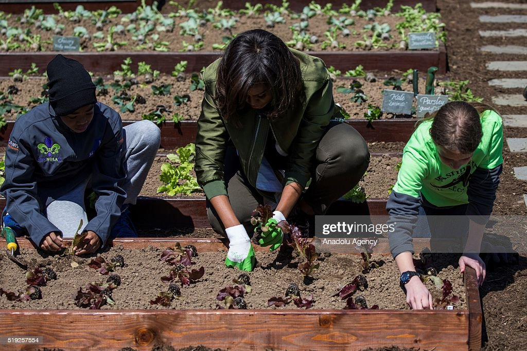 First Lady Michele Obama plants lettuce with Erin Hinson and Malik Robins in the 2016 White House Kitchen Garden in Washington USA on April 5 2016
