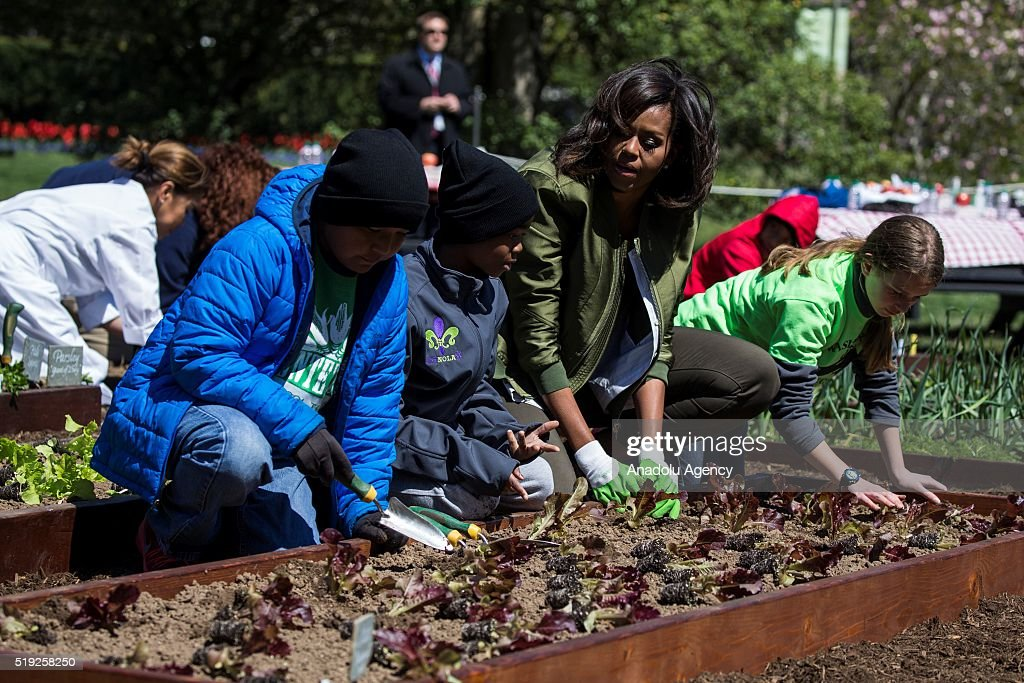 First Lady Michele Obama points to another section of the garden while planting lettuce with Miles Frost Malik Robins and Erin Hinson in the 2016...