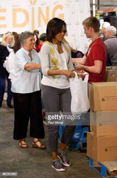 First lady Michelle Obama along with congressional spouses and volunteers fills plastic bags with nonperishable food items for distribution at the...