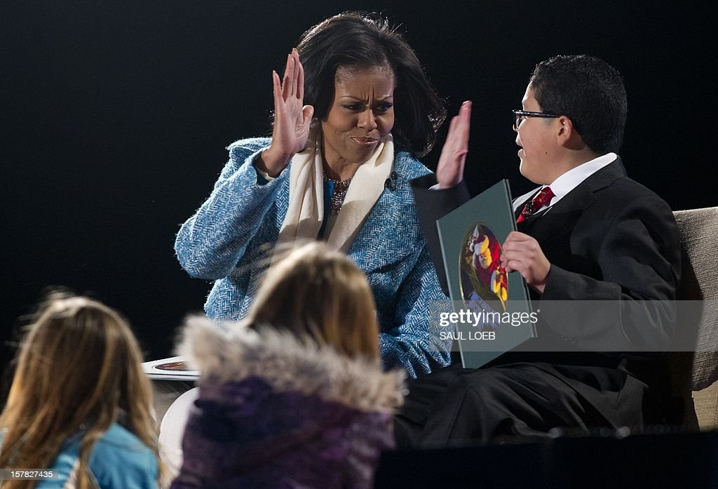 First Lady Michelle Obama and actor Rico Rodriguez (R) from the televison show 'Modern Family' high five after reading 'Twas the Night Before Christmas' during the National Christmas Tree Lighting on the Ellipse adjacent to the White House in Washington, DC, on December 6, 2012. The annual event, hosted by Harris, features US President Barack Obama and performances by Jason Mraz, Ledisi, James Taylor, Kenny 'Babyface' Edmonds, Colbie Caillat and American Idol season 11 winner Phillip Phillips. AFP PHOTO / Saul LOEB