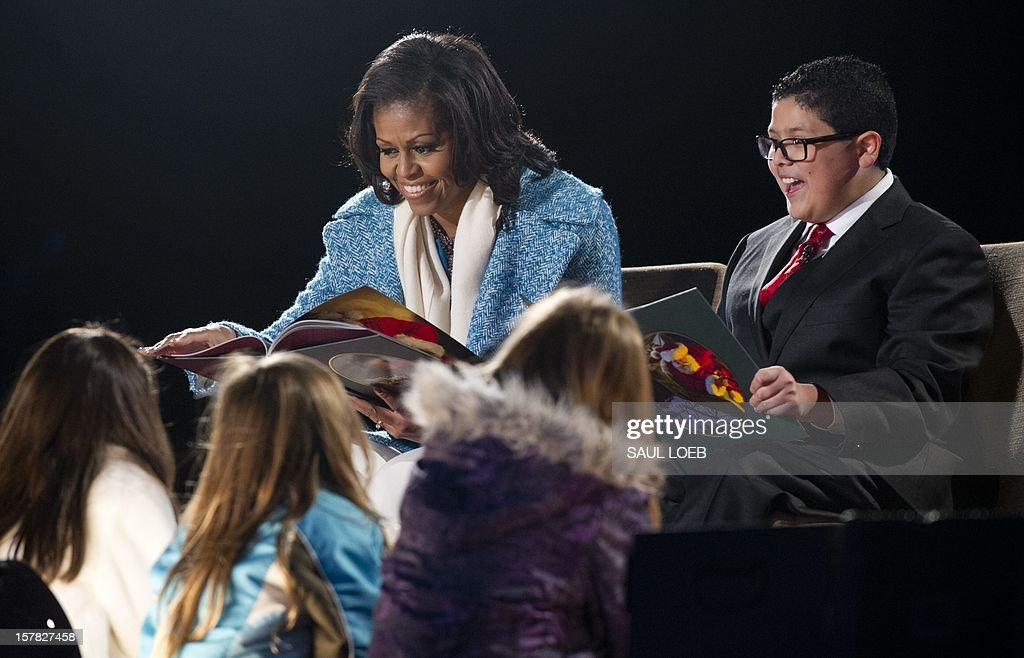 First Lady Michelle Obama and actor Rico Rodriguez (R) from the televison show 'Modern Family' read 'Twas the Night Before Christmas' during the National Christmas Tree Lighting on the Ellipse adjacent to the White House in Washington, DC, on December 6, 2012. The annual event, hosted by Harris, features US President Barack Obama and performances by Jason Mraz, Ledisi, James Taylor, Kenny 'Babyface' Edmonds, Colbie Caillat and American Idol season 11 winner Phillip Phillips. AFP PHOTO / Saul LOEB