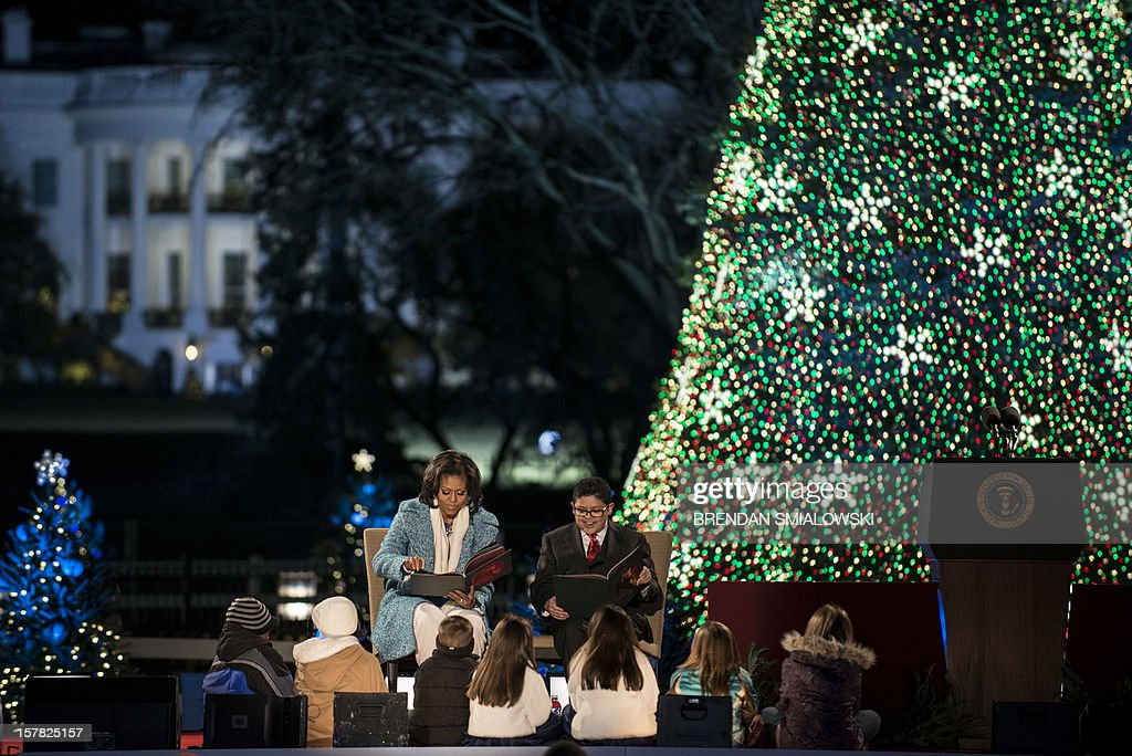 US First Lady Michelle Obama and actor Rico Rodriguez read The Night Before Christmas during the 90th annual National Christmas Tree Lighting on the Ellipse of the National Mall December 6, 2012 in Washington, DC. US President Barack Obama and others attended the event which included entertainment before the lighting of the National Christmas Tree. AFP PHOTO/Brendan SMIALOWSKI