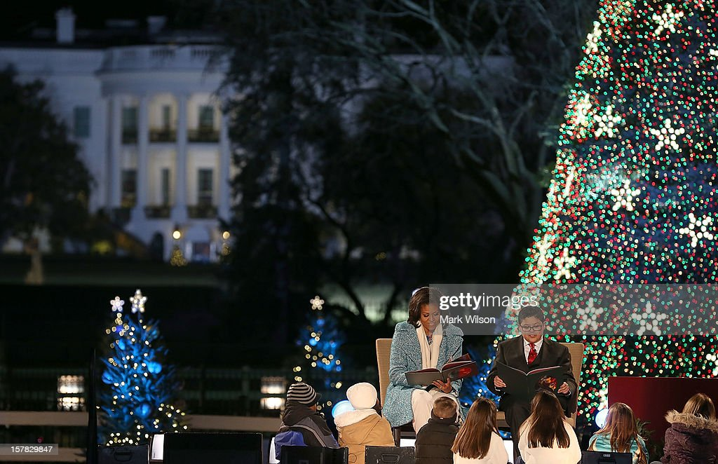 First lady Michelle Obama (L), and actor Rico Rodriguez (R), reads Christmas books to children during the annual lighting of the National Christmas tree on December 6, 2012 in Washington, DC. This year is the 90th annual National Christmas Tree Lighting Ceremony.