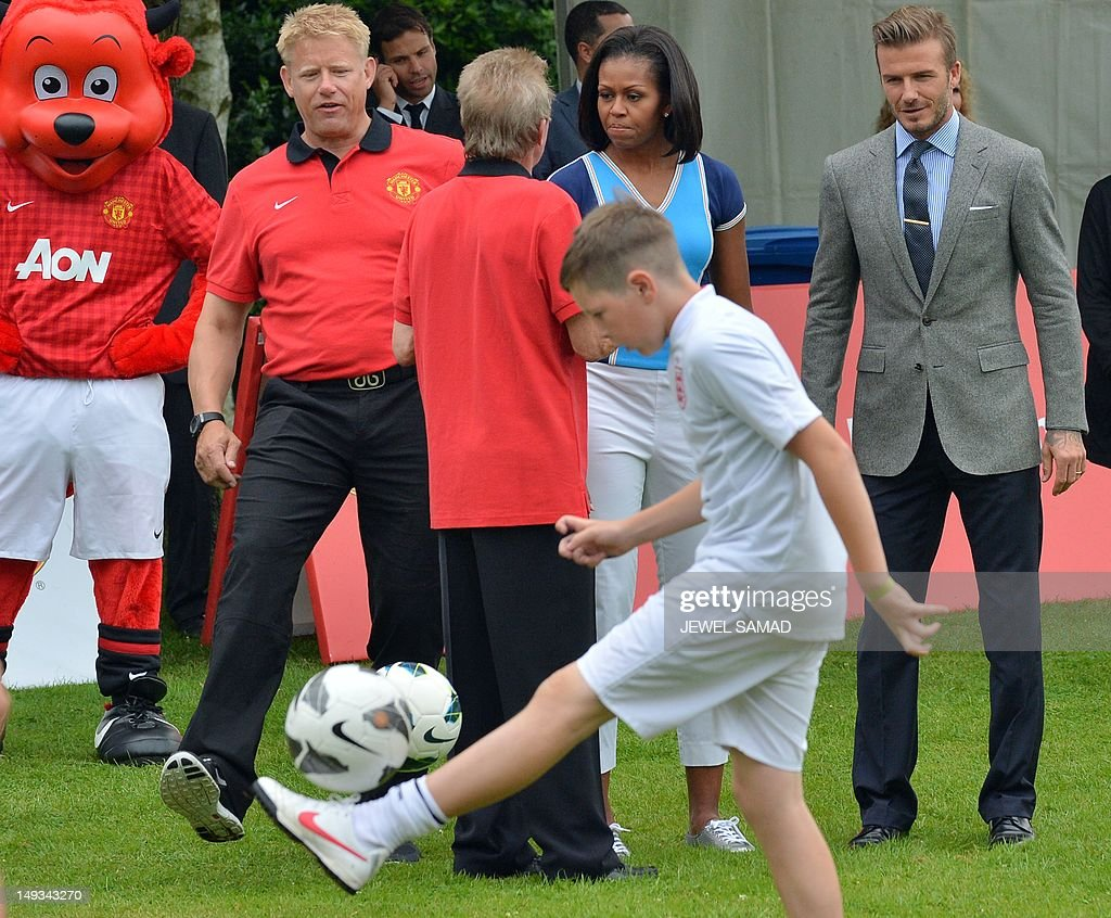 US First Lady Michelle Obama and British footballer David Beckham watch children playing football during the 'Let's Move-London' event at the Winfield House in London on July 27, 2012, hours before the official start of the London 2012 Olympic Games.