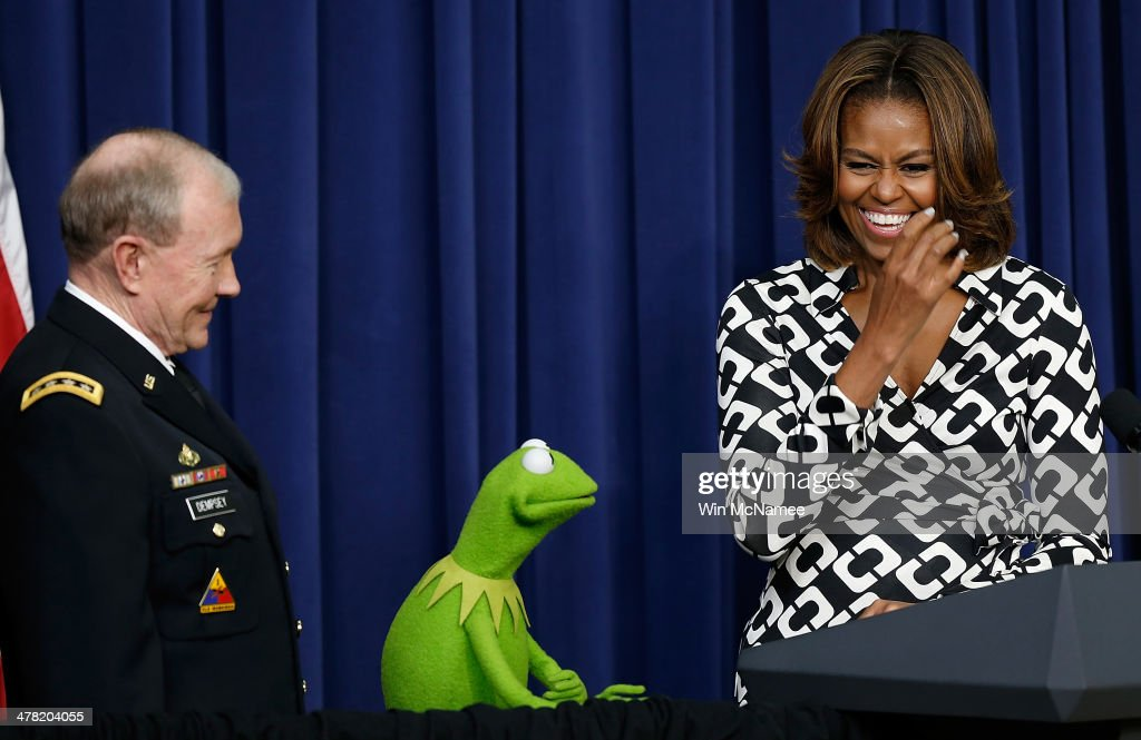 U.S. first lady Michelle Obama (R) and Chairman of the Joint Chiefs of Staff Gen. Martin Dempsey (L) welcome Kermit the Frog during a screening of Disney's 'Muppets Most Wanted' at the Eisenhower Executive Office Building March 12, 2014 in Washington, DC. The movie's preview was for an audience of military children and families as part of the Joining Forces Initiative.
