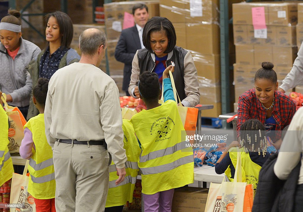 First Lady Michelle Obama and daughters Sasha (R) and Malia (2nd L) distribute food items at the Capitol Area Food Bank on November 21, 2012, a day ahead of Thanksgiving, in Washington, DC. AFP PHOTO/Mandel NGAN