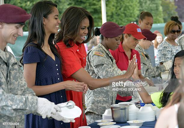 US First Lady Michelle Obama and her daughter Malia joke with children during a lunch at the United States and Nato military base in Vicenza northern...