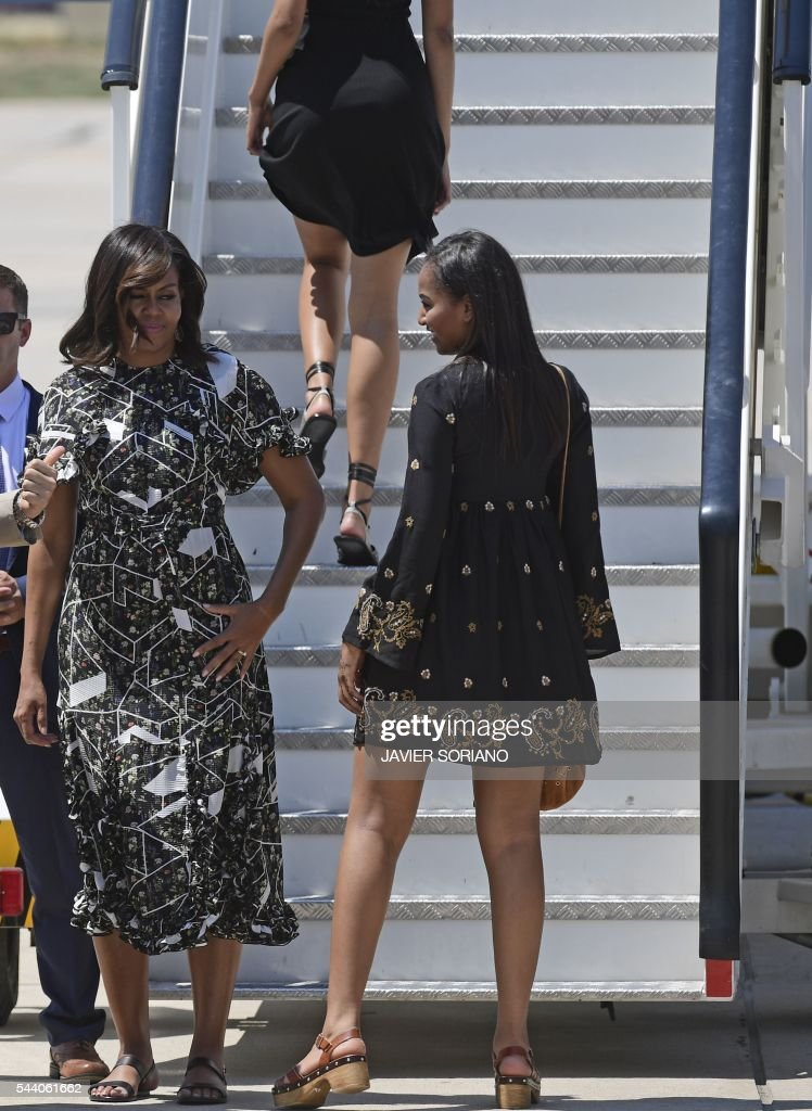 US first lady Michelle Obama (L)and her daughters Malia (R)and Sasha (UP) board an aircraft at the Torrejon airbase near Madrid on June 29, 2016 a day after presenting the 'Let Girls Learn' initiative . First Lady Michelle Obama began a two day visit to Spain by delivering a speech on the education initiative launched in March 2015 to help adolescent girls across the world access a quality education. / AFP / JAVIER