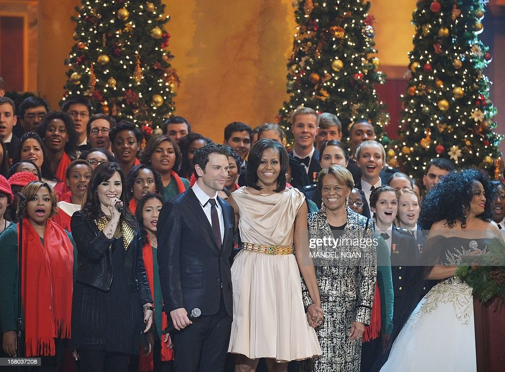 US First Lady Michelle Obama and her mother Marian Robinson (2ndR) sing a Christmas carol with Actress/singer Demi Lovato (2nd R), singer Chris Mann (3rd R) and Diana Ross (R) during the taping of the 'Christmas in Washington' television special on December 9, 2012 at the Building Museum in Washington, DC. AFP PHOTO/Mandel NGAN