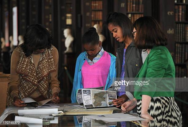 US First Lady Michelle Obama and her two daughters Sasha and Malia look through documents with genealogist Fiona Fitsimons in the archives during a...