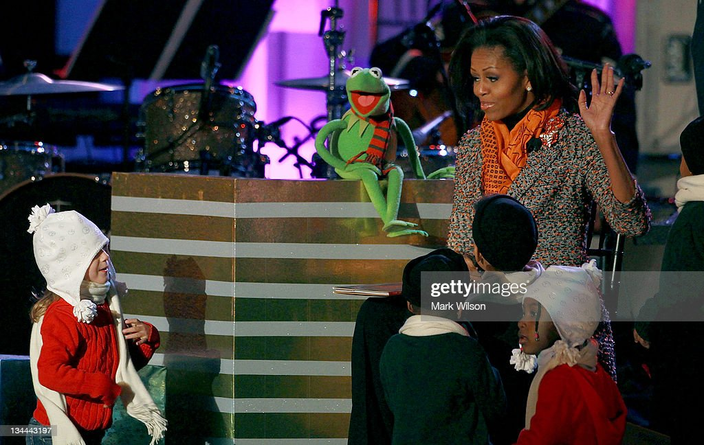 First lady <a gi-track='captionPersonalityLinkClicked' href=/galleries/search?phrase=Michelle+Obama&family=editorial&specificpeople=2528864 ng-click='$event.stopPropagation()'>Michelle Obama</a> and Kermit the frog read a book to children during the National Christmas Tree lighting ceremony, on December 1, 2011 at the Ellipse, south of the White House, in Washington, DC. The first family participated in the 89th annual National Christmas Tree Lighting Ceremony.