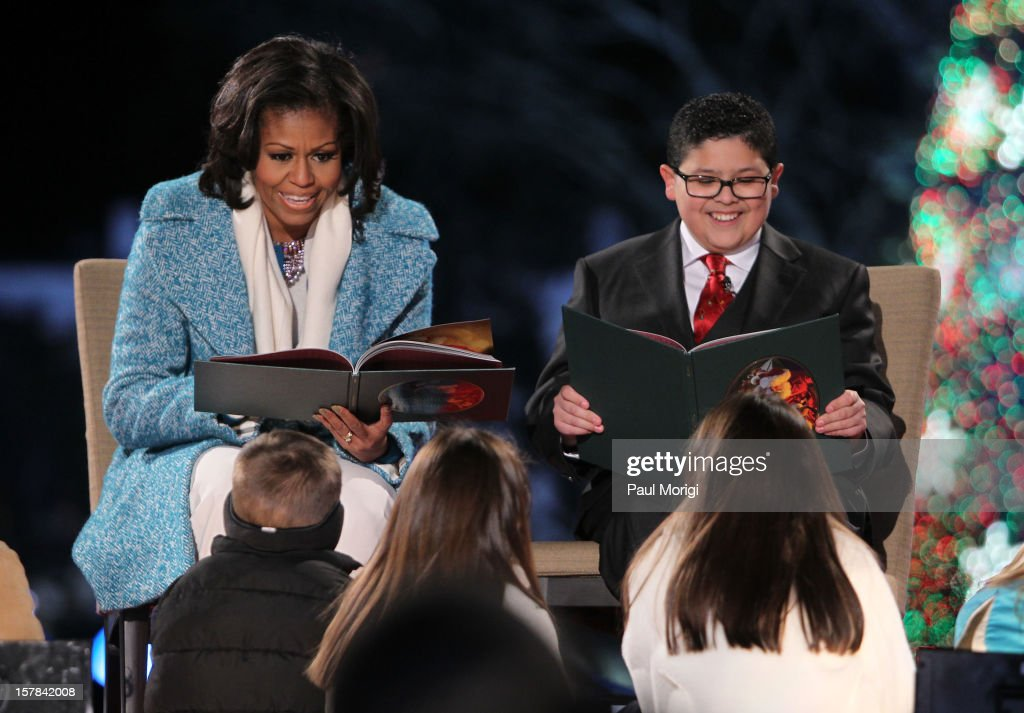 First Lady <a gi-track='captionPersonalityLinkClicked' href=/galleries/search?phrase=Michelle+Obama&family=editorial&specificpeople=2528864 ng-click='$event.stopPropagation()'>Michelle Obama</a> and Modern Family's Rico Rodriguez read a Christmas story to children onstage at the 2012 National Christmas Tree Lighting Ceremony at President's Park on December 6, 2012 in Washington, DC.