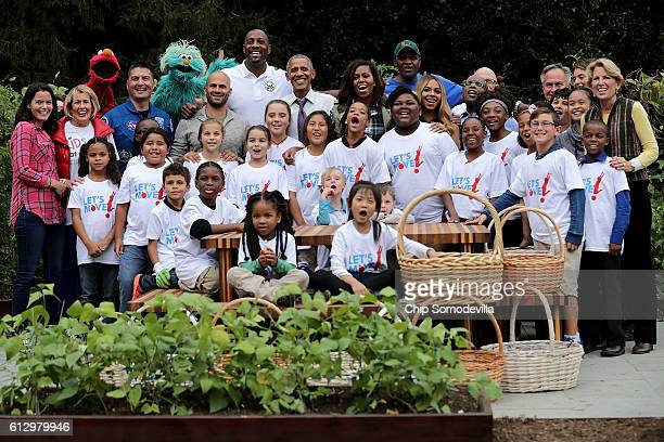 S first lady Michelle Obama and President Barack Obama pose for a group photograph during an event to harvest the White House Kitchen Garden on the...