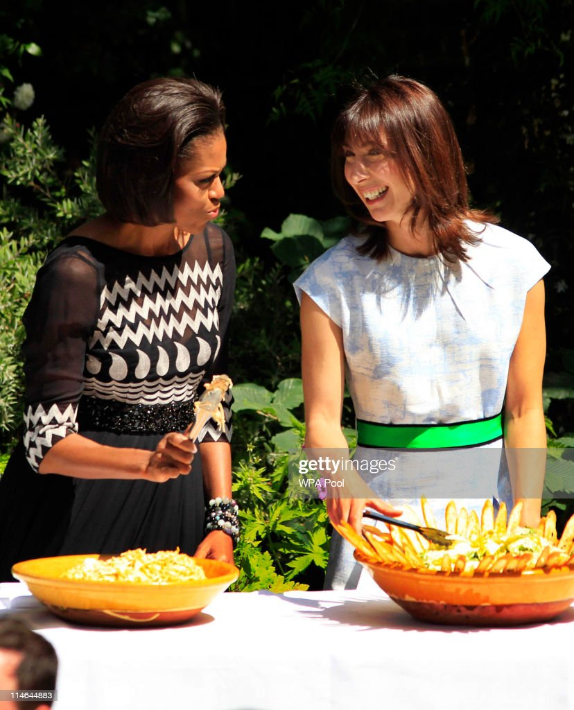 US first lady Michelle Obama (L) and Samantha Cameron, wife of Britain's Prime Minister David Cameron, chat as they serve food to members of the military during a barbecue in the garden of 10 Downing Street on May 25, 2011 in London, England. The 44th President of the United States, Barack Obama, and his wife Michelle are in the UK for a two day State Visit at the invitation of HM Queen Elizabeth II. Last night they attended a state banquet at Buckingham Palace and today's events include talks at Downing Street and the President will address both houses of parliament at Westminster Hall.