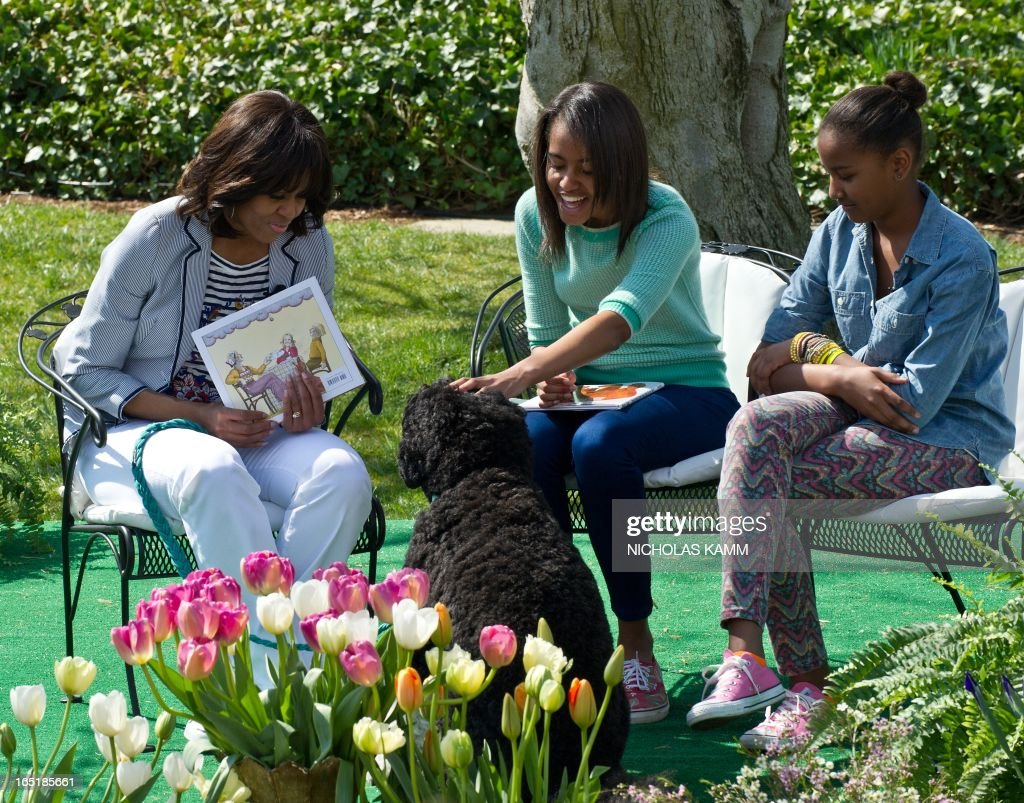 US First Lady Michelle Obama (L) and younger daughter Sasha (R) look on as elder daughter Malia (C) pets Bo, the first family's dog, during the annual White House Easter Egg Roll in Washington on April 1, 2013. AFP PHOTO/Nicholas KAMM