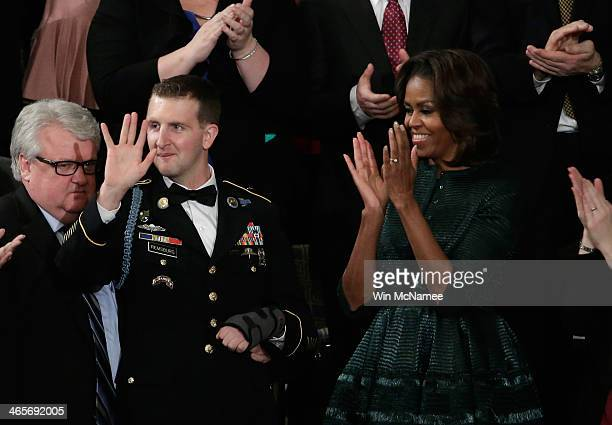 First lady Michelle Obama applauds as US Army Ranger Sergeant First Class Cory Remsburg is acknowledged by US President Barack Obama during the State...