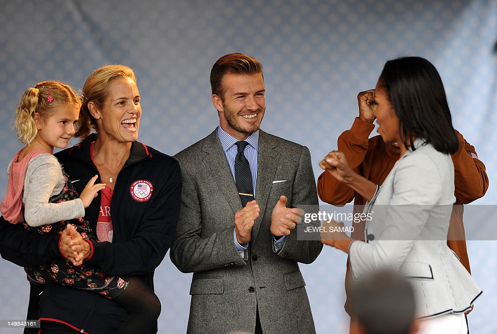 US First Lady Michelle Obama (R) arrives applauded by British footballer David Beckham (C) during a 'Let's Move-London' event at the Winfield House in London on July 27, 2012, hours before the official start of the London 2012 Olympic Games.