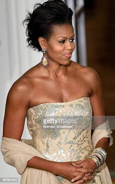 First lady Michelle Obama awaits the arrival of the Indian Prime Minister in the North Portico of the White House November 24 2009 in Washington DC...