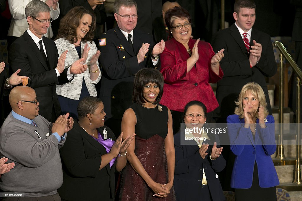 U.S. First Lady <a gi-track='captionPersonalityLinkClicked' href=/galleries/search?phrase=Michelle+Obama&family=editorial&specificpeople=2528864 ng-click='$event.stopPropagation()'>Michelle Obama</a>, bottom center, stands as Tim Cook, chief executive officer of Apple Inc., top left, looks on before U.S. President Barack Obama, unseen, delivers the State of the Union address to a joint session of Congress at the Capitol in Washington, D.C., U.S., on Tuesday, Feb. 12, 2013. Obama called for raising the federal minimum wage to $9 an hour and warned he'll use executive powers to get his way on issues from climate change to manufacturing if Congress doesn't act, laying out an assertive second-term agenda sure to provoke Republicans. Photographer: Andrew Harrer/Bloomberg via Getty Images
