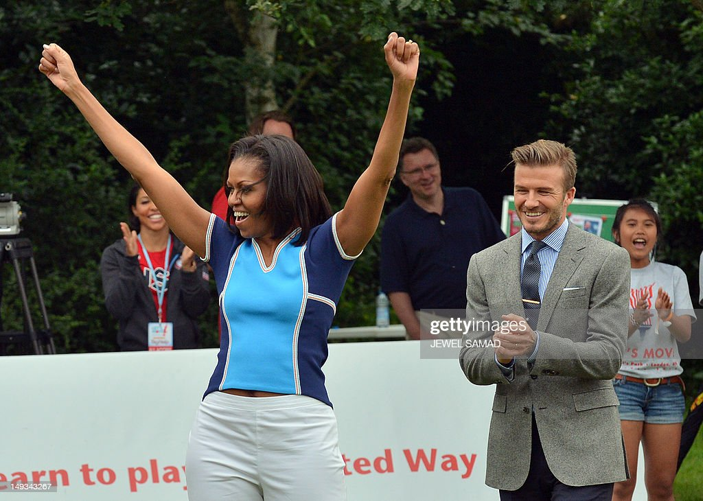 US First Lady Michelle Obama celebrates after kicking a ball to goal as British footballer David Beckham applauds during the 'Let's Move-London' event at the Winfield House in London on July 27, 2012, hours before the official start of the London 2012 Olympic Games.
