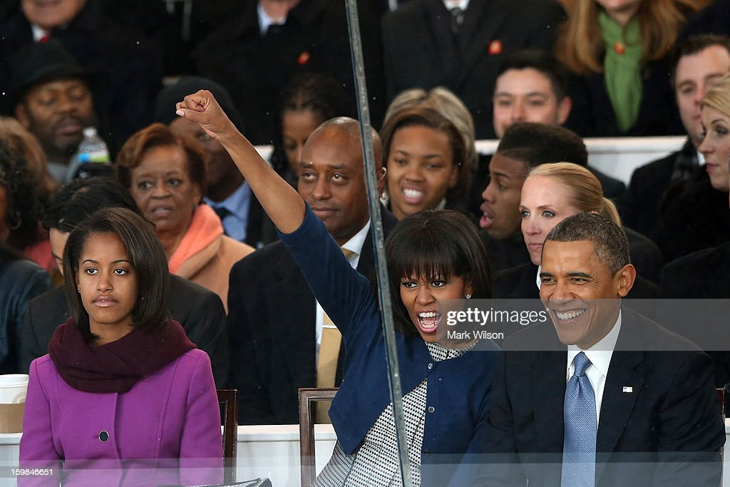 First lady Michelle Obama (C) cheers as Malia Obama (L) and U.S. President Barack Obama watch from the reviewing stand as the presidential inaugural parade winds through the nation's capital January 21, 2013 in Washington, DC. Barack Obama was ceremonially sworn in for a second term as President of the United States.