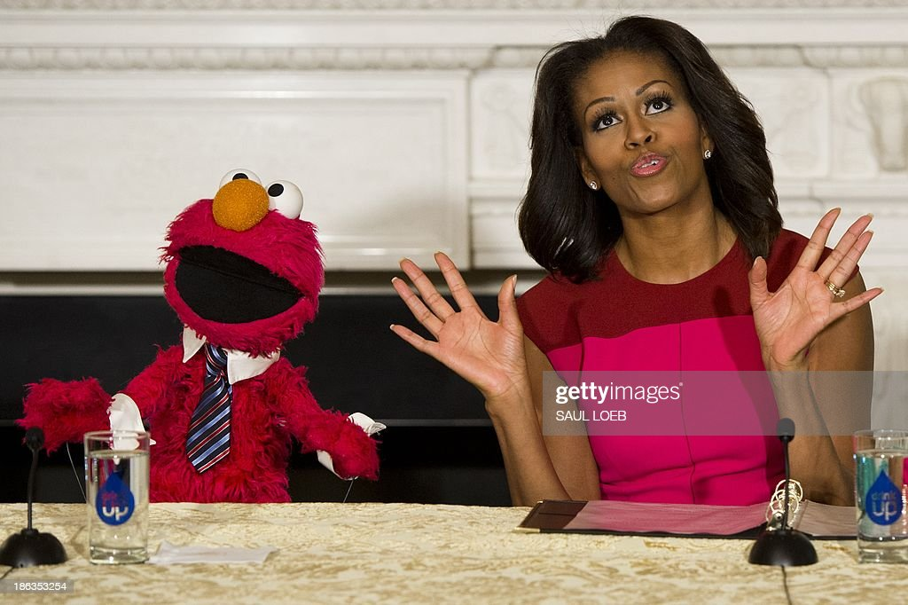 US First Lady Michelle Obama dances alongside Sesame Street character Elmo during an event announcing free licensing of Sesame Street characters to promote and market fresh fruit and vegetables by Produce Marketing Association growers, suppliers and retailers, as part of the Let's Move initiative, in the State Dining Room of the White House in Washington, DC, October 30, 2013. The agreement utilizes the strength of the Sesame Street brand to help deliver messages about fresh fruits and vegetables and characters such as Elmo and Big Bird may be on produce in stores as early as mid-2014. AFP PHOTO / Saul LOEB