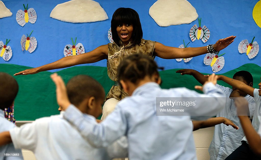U.S. first lady <a gi-track='captionPersonalityLinkClicked' href=/galleries/search?phrase=Michelle+Obama&family=editorial&specificpeople=2528864 ng-click='$event.stopPropagation()'>Michelle Obama</a> dances with pre-kindergarten students while she visits the Savoy School May 24, 2013 in Washington, DC. The Savoy School, once one of the lowest performing schools in the District of Columbia, has shown significant signs of improvement since being designated as one of eight schools selected last year for the Turnaround Arts Initiative by the President's Committee on the Arts and the Humanities.