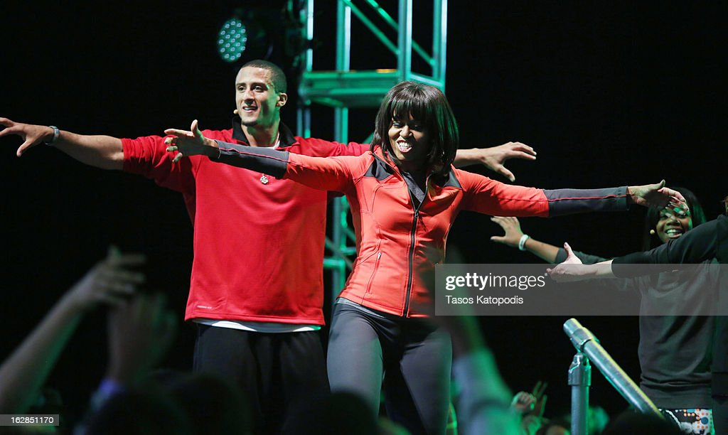 First lady Michelle Obama (R) dances with San Francisco 49ers quarterback Colin Kaepernick during a debut of a school exercise program February 28, 2013 in Chicago, Illinois. Obama unveiled a new initiative called 'Let's Move Active Schools' to help schools create a physical activity programs for students.