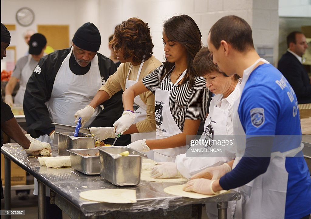 US First Lady Michelle Obama daughter Malia and senior advisor to the president Valerie Jarrett make burrittos while taking part in a community...