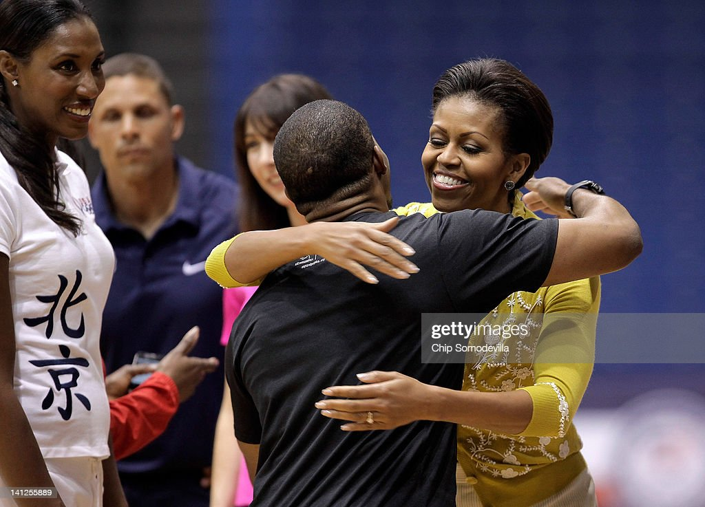 First Lady <a gi-track='captionPersonalityLinkClicked' href=/galleries/search?phrase=Michelle+Obama&family=editorial&specificpeople=2528864 ng-click='$event.stopPropagation()'>Michelle Obama</a> (R) embraces American Paralympic athlete and Iraq War Veteran Kortney Clemons during an Olympics-themed event with area school children at American University March 13, 2012 in Washington, DC. Fifth graders from MacFarland Middle School in Washington, D.C., Manor View Elementary School in Maryland and Arlington Science Focus School in Virginia participated in a mini-Olympics competition in celebration of the 2012 London Summer Olympics and Mrs. Obama's Let's Move! initiative.