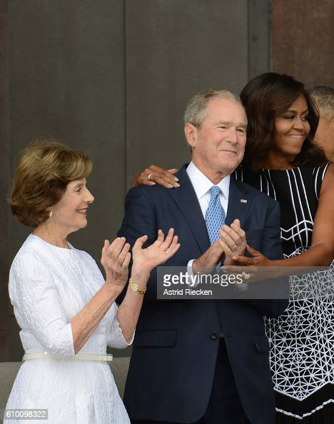 First lady Michelle Obama embraces former president George W Bush accompanied by his wife former first lady Laura Bush while participating in the...