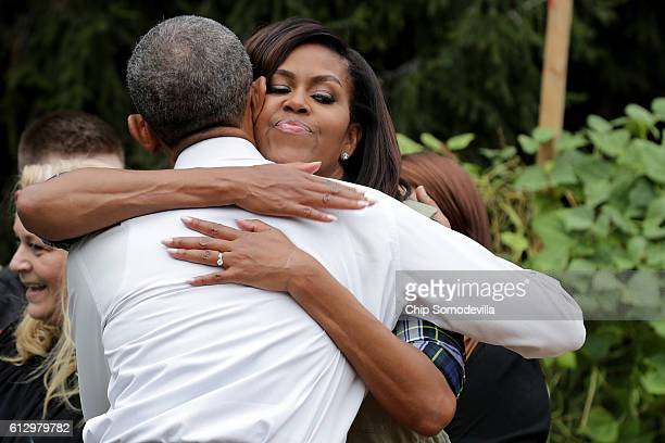 S first lady Michelle Obama embraces President Barack Obama during an event to harvest the White House Kitchen Garden on the South Lawn of the White...