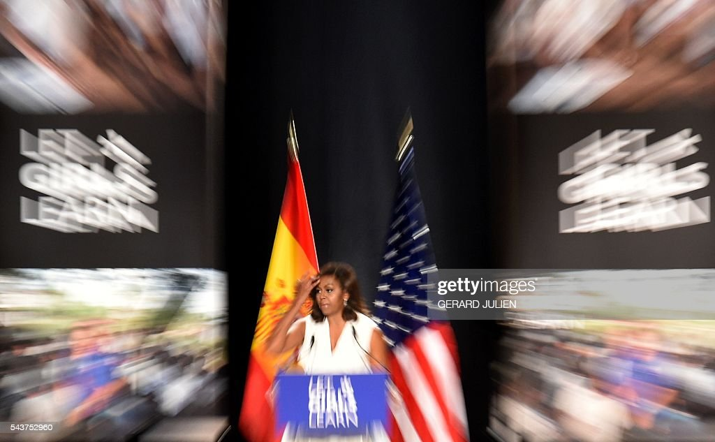 US first lady Michelle Obama gestures as she delivers a speech presenting the 'Let Girls Learn' initiative on June 29, 2016 in Madrid. First Lady Michelle Obama began a two day visit to Spain by delivering a speech on the education initiative launched in March 2015 to help adolescent girls across the world access a quality education. / AFP / GERARD