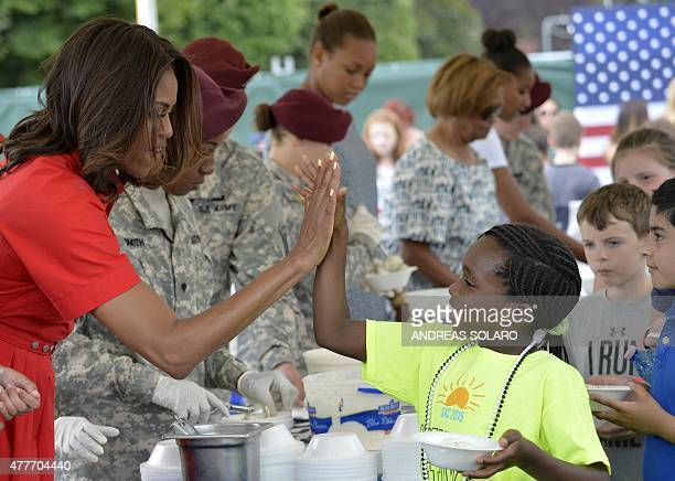 US First Lady Michelle Obama gestures as she distributes food to children at the United States and Nato military base in Vicenza northeastern Italy...