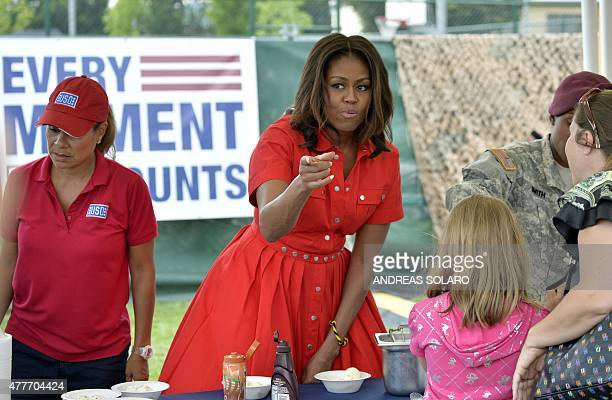 US First Lady Michelle Obama gestures as she distributes food to people at the United States and Nato military base in Vicenza northern Italy on June...