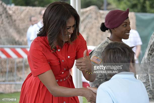 US First Lady Michelle Obama gives a thumbs up as she shakes hands with a child at the United States and Nato military base in Vicenza northeastern...