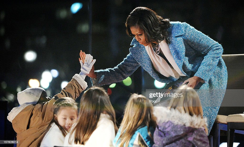 First lady <a gi-track='captionPersonalityLinkClicked' href=/galleries/search?phrase=Michelle+Obama&family=editorial&specificpeople=2528864 ng-click='$event.stopPropagation()'>Michelle Obama</a> gives high five to kids after reading a story during the 90th National Christmas Tree Lighting Ceremony on the Ellipse behind the White House on December 6, 2012 in Washington, DC. This year is the 90th annual National Christmas Tree Lighting Ceremony.