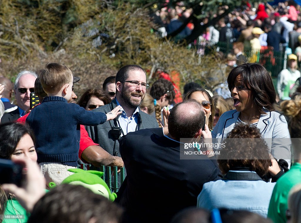 US First Lady Michelle Obama (R) greets a child as she arrives at a cooking station during the annual White House Easter Egg Roll in Washington on April 1, 2013. AFP PHOTO/Nicholas KAMM