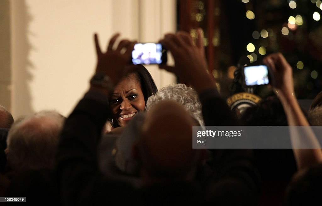 First lady <a gi-track='captionPersonalityLinkClicked' href=/galleries/search?phrase=Michelle+Obama&family=editorial&specificpeople=2528864 ng-click='$event.stopPropagation()'>Michelle Obama</a> greets guests following a Hanukkah reception in the Grand Foyer of the White House December 13, 2012 in Washington DC. The celebration included the lighting of candles in a 90-year-old menorah from a temple in Long Island, New York that was heavily flooded during Superstorm Sandy.