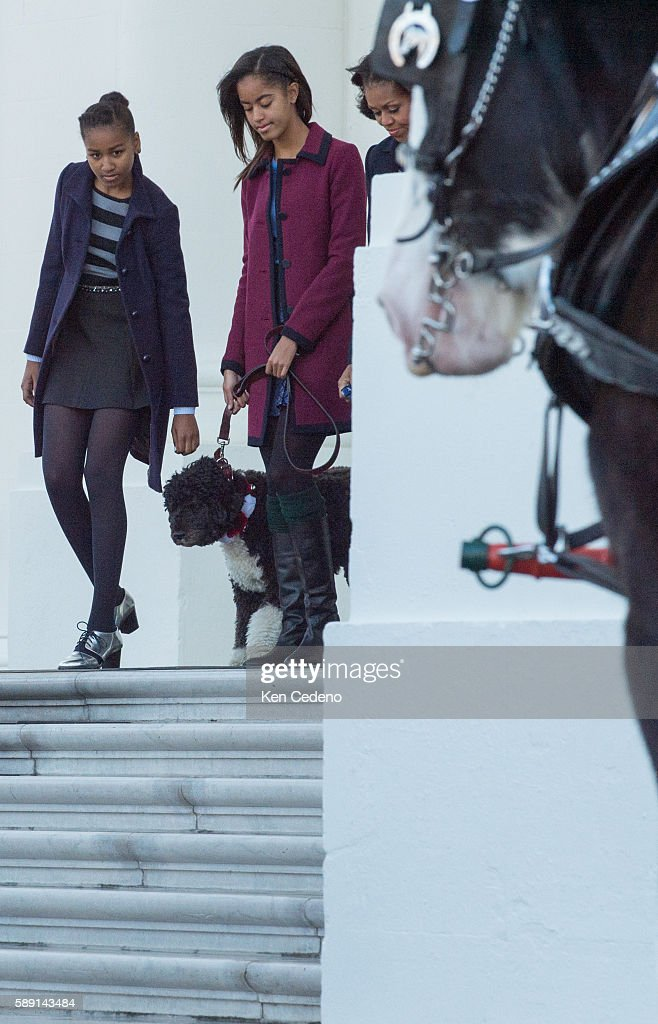 First Lady Michelle Obama her daughters Sasha Obama and Malia Obama the family dogs Bo and Sunny walk out of the White House North Portico to receive...