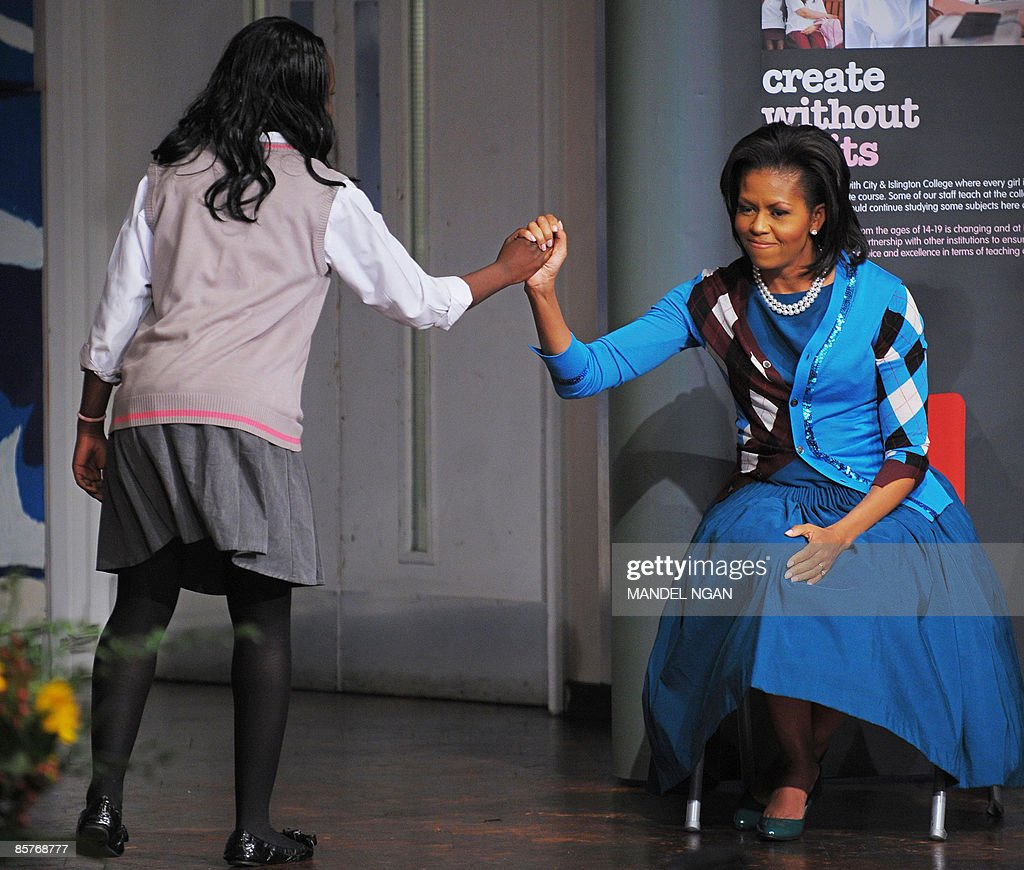 US First Lady Michelle Obama (R) high fives student Brenda Mensah after she sang a song during a visit to the Elizabeth Garrett Anderson Language School in London, on April 2, 2009. Michelle Obama dared touch Queen Elizabeth II, but the US first lady has made such an impact in Britain that she was spared the media savaging that has gone with previous breaches of royal protocol. The pair met at Buckingham Palace on Wednesday. The British monarch put her arm around the waist of President's Barack Obama's wife. The much taller first lady responded by putting an arm around the queen. AFP PHOTO/Mandel NGAN