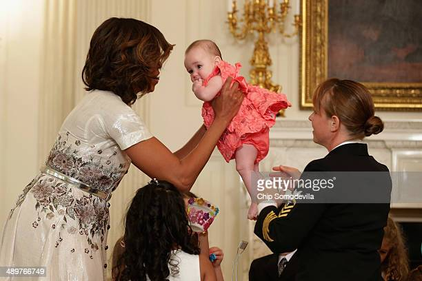 First lady Michelle Obama holds a military mom's baby while helping children make crafts in the State Dining Room during the annual Mother's Day tea...