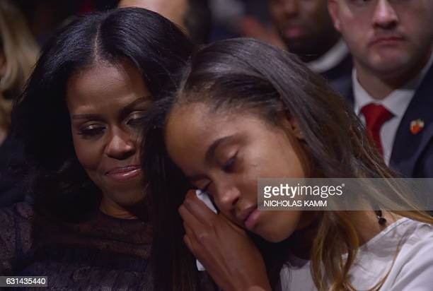 US first lady Michelle Obama holds her daughter Malia as US President Barack Obama speaks during his farewell address in Chicago Illinois on January...