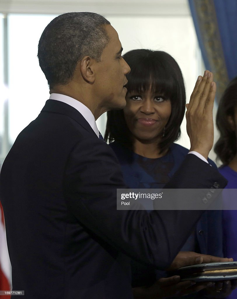 First Lady <a gi-track='captionPersonalityLinkClicked' href=/galleries/search?phrase=Michelle+Obama&family=editorial&specificpeople=2528864 ng-click='$event.stopPropagation()'>Michelle Obama</a> holds the family bible as U.S. President <a gi-track='captionPersonalityLinkClicked' href=/galleries/search?phrase=Barack+Obama&family=editorial&specificpeople=203260 ng-click='$event.stopPropagation()'>Barack Obama</a> is officially sworn-in by Chief Justice John Roberts Jr. in the Blue Room of the White House during the 57th Presidential Inauguration January 20, 2013 in Washington, D.C. Obama and U.S. Vice President Joe Biden were officially sworn in a day before the ceremonial inaugural swearing-in.