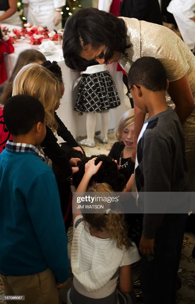 First Lady Michelle Obama (R) holds the presidential dog Bo as young children pet him during the first viewing of the White House 2012 holiday decorations in Washington, DC, November 28, 2012. AFP Photo/Jim WATSON
