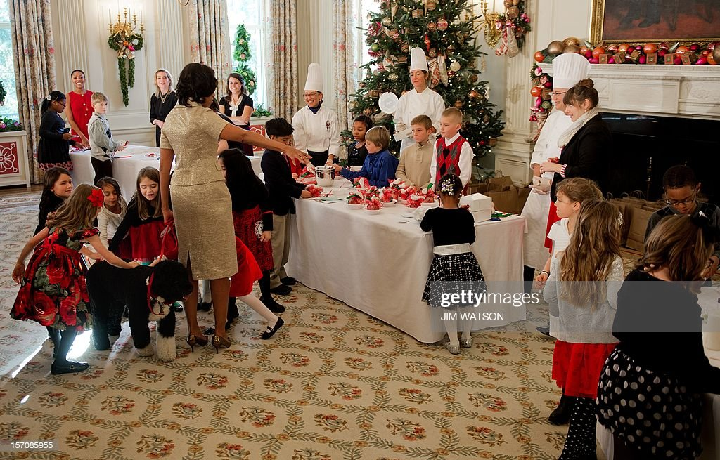 First Lady Michelle Obama (C) holds the presidential dog Bo on his leash as young children run in to pet him during the first viewing of the White House 2012 holiday decorations in Washington, DC, November 28, 2012. AFP Photo/Jim WATSON